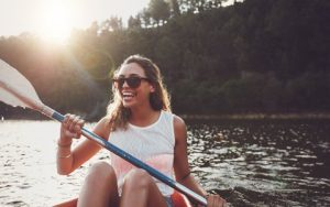 Woman in Canoe Smiling About Dental Crowns and Bridges from Hillsboro Dental Excellence