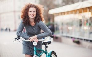 Woman on Bike Considers All on 4 Dental Implants with Hillsboro Dental Excellence