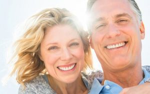 Smiling Couple with Fixed Implant Bridges from Hillsboro Dental Excellence